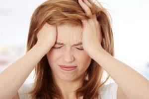 Женщина страдает головными болями