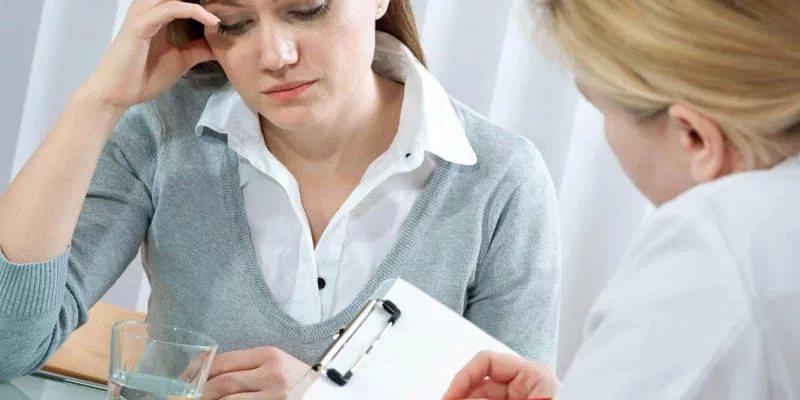 Женщина озвучивает симптомы на приеме у врача