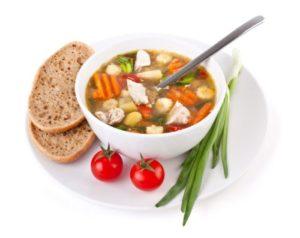 Суп из овощей в тарелке, с хлебом, луком и помидорами