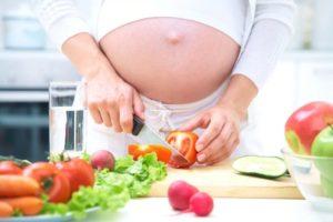 Беременная женщина режет помидоры на салат